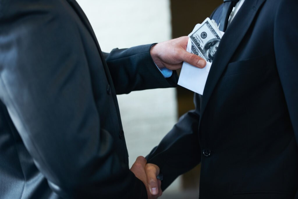 An organized crime concept with two men shaking hands while one man is secretly slipping an envelope filled with US Dollar banknotes onto the other man's suit.